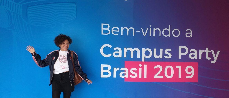 Amanda Guimarães do Plano de Menina posa em frente a um painel de boas-vindas.